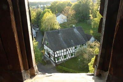 Blick durchs Kirchturmfenster auf das alte Fachwerkpfarrhaus neben der Oberholzklauer Kirche (Quelle: Homepage des ev. Kirchenkreis Siegen)