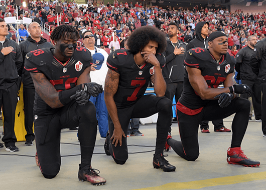 San Francisco 49ers Eli Harold, Colin Kaepernick, and Eric Reid kneel before a game against the Arizona Cardinals, October 07, 2016 (Source: Kirby Lee/The Nation)
