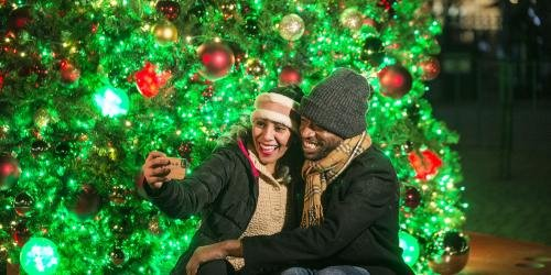 Guests taking a selfie in front of a christmas tree