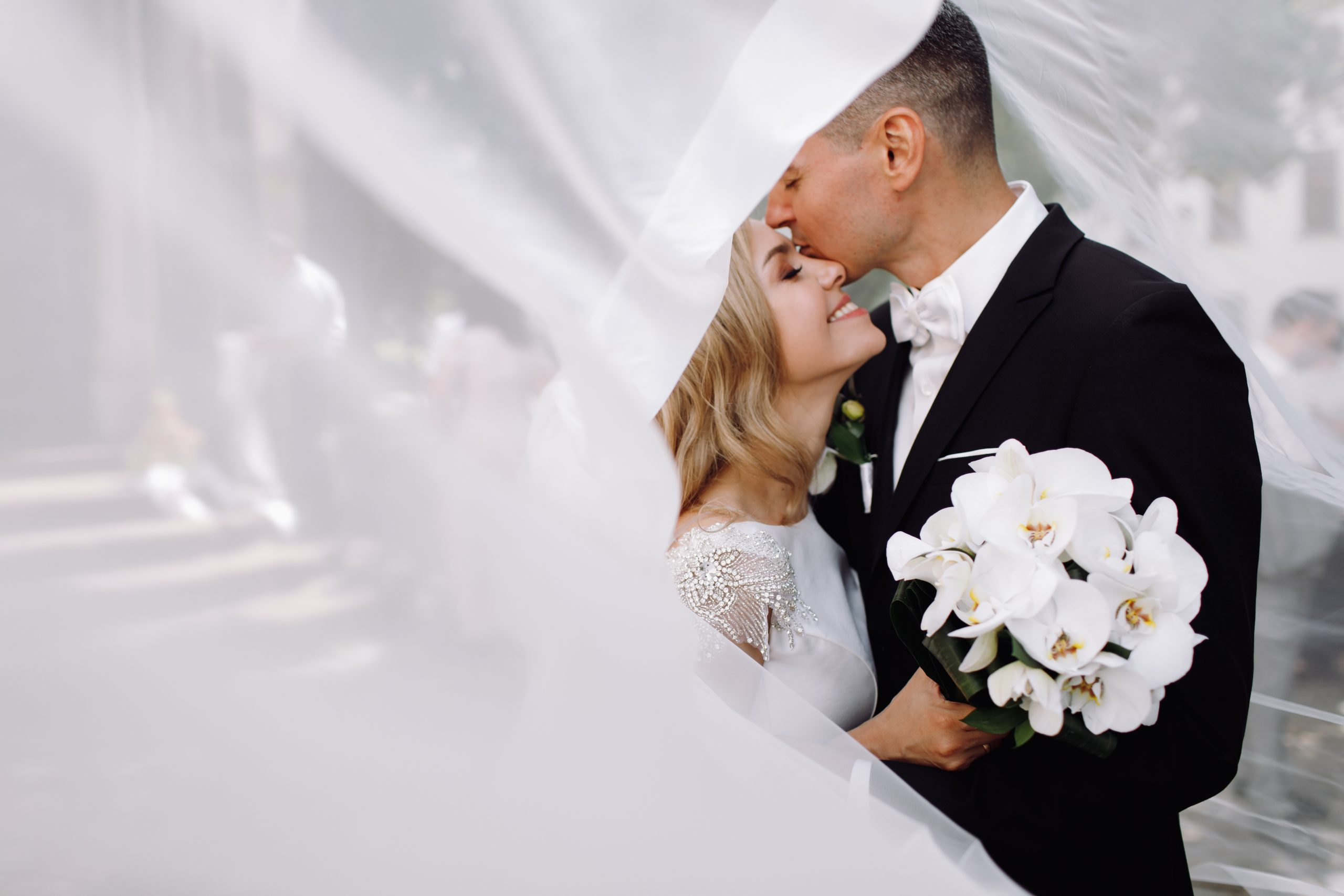 Groom in black tuxedo hugs tender stunning bride while they stan