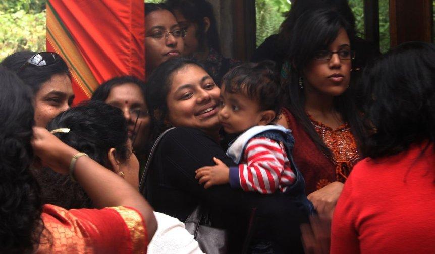 Female devotees dressed in saris wait for the Lord Murugan Temple to open at Skanda Vale Ashram