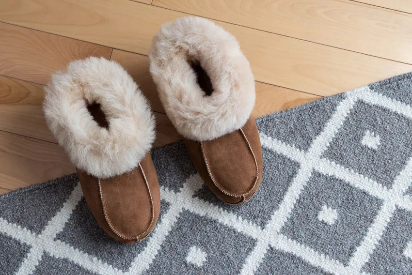 A comfortable pair of slippers on a grey woven rug