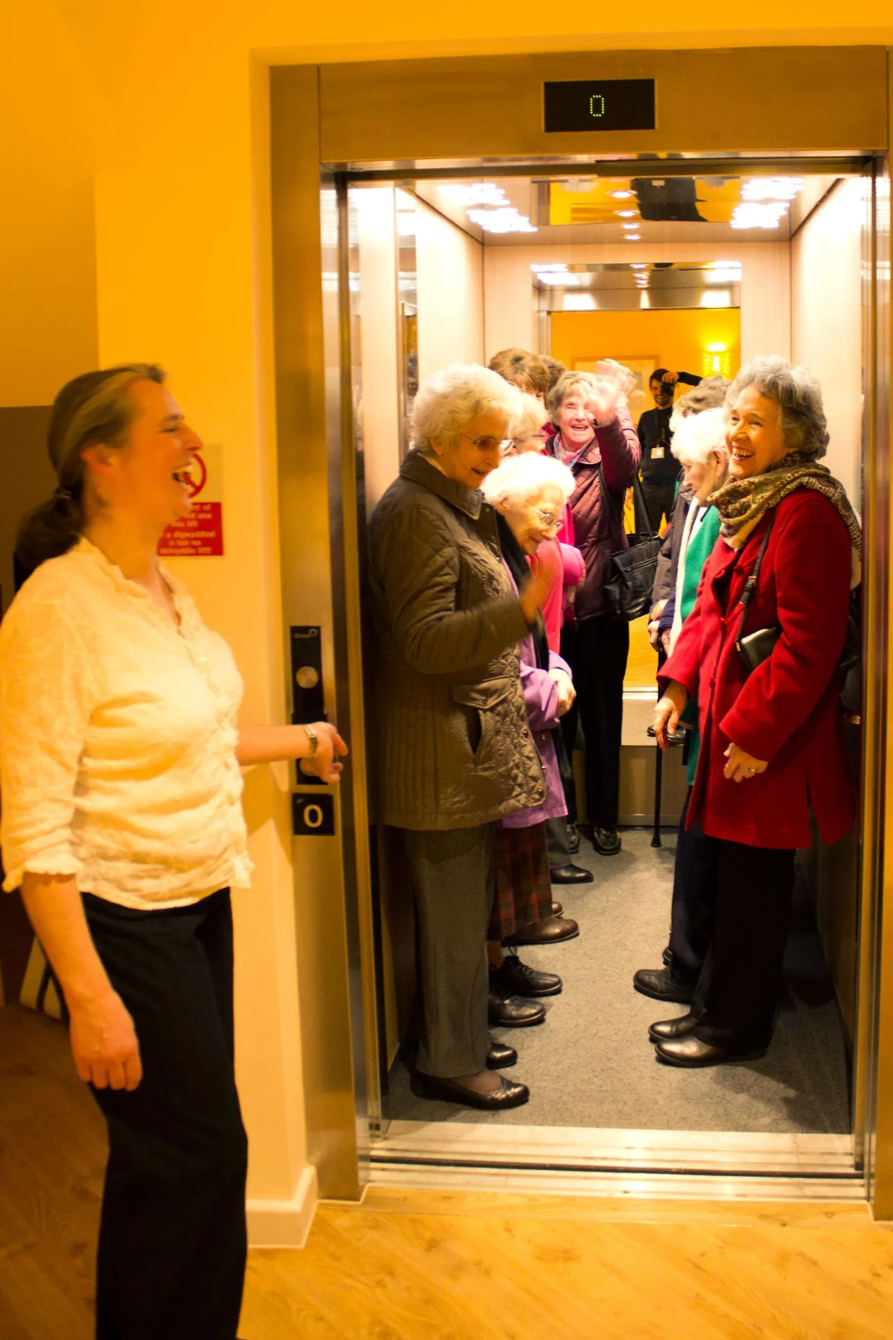 A group of ladies laughing in the lift at an open day at Skanda Vale Hospice