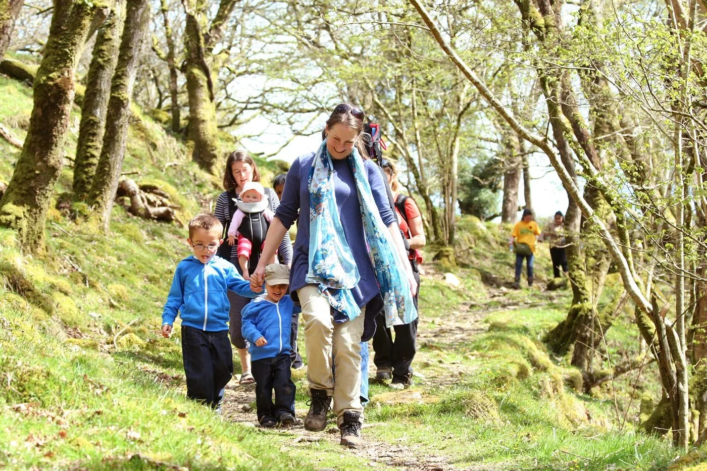 Woman with young children on a sponsored walk for Skanda Vale Hospice in Ty Canol woods, Pembrokeshire