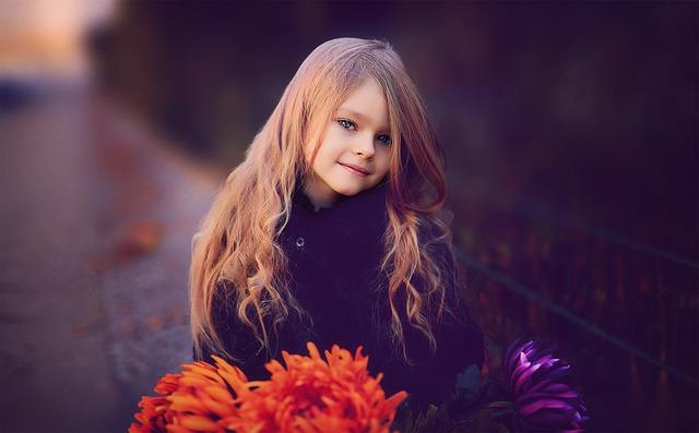 ein hübsches Mädchen mit roten Blumen im Vordergrund, lange blonde Haare