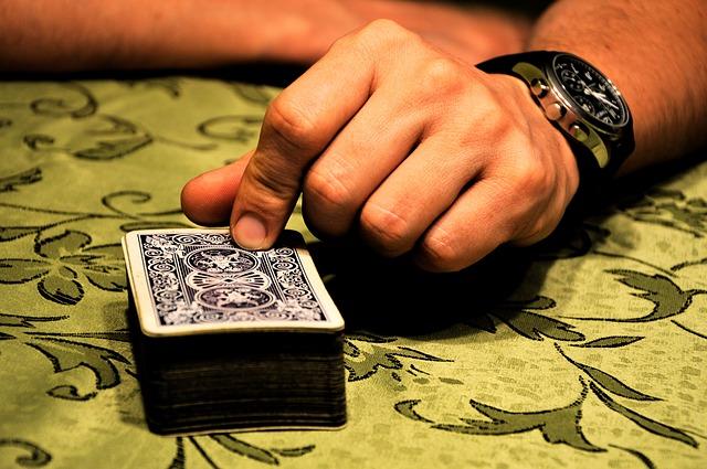 Kartenstapel liegt, Mann tippt drauf und hält sie nach unten gedrückt