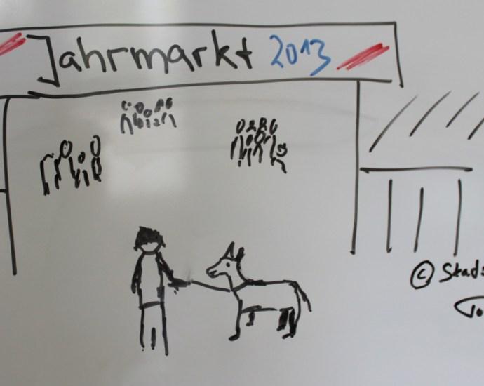 Am Whiteboard gezeichneter Mann vor dem Tore eines Jahrmarkts mit einer Zicke an der Leine