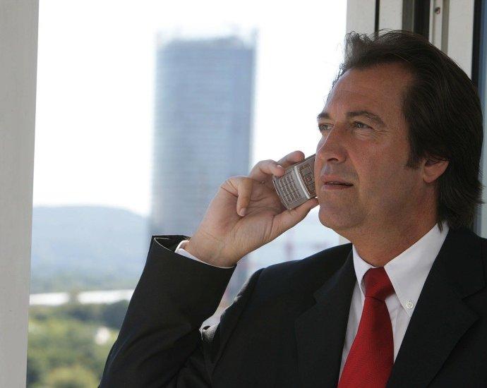 Ein mann mit Telefon in der Hand mit Anzug Chef Hochhaus gebäude