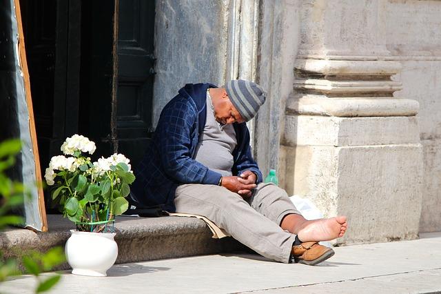 Mann schläft in Rom vor einer Kirche