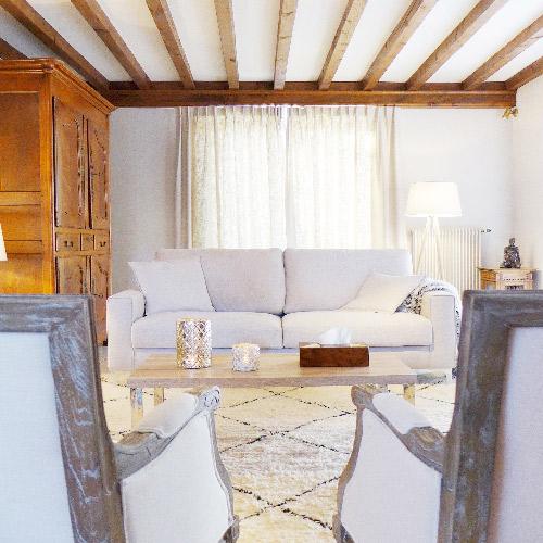 Réalisation du studio d'architecture et de décoration Skéa Designer. Derrière deux fauteuils ancien en bois et lin, une table basse, un tapis berbère, un canapé beige et quelques accessoires argenté. La cheminée ancienne, les poutres apparentes , l'armoire familiale donnent du cachet à la maison.