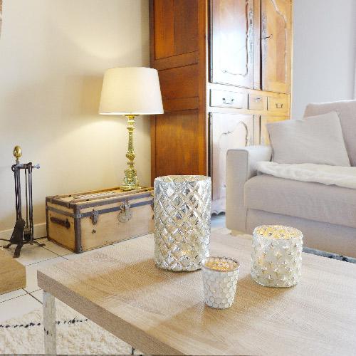 Réalisation du studio d'architecture et de décoration Skéa Designer. Des accessoires décoratifs rappellent le pieds argenté de la table basse. Au loin, une lampe argentée est posée sur une malle ancienne.
