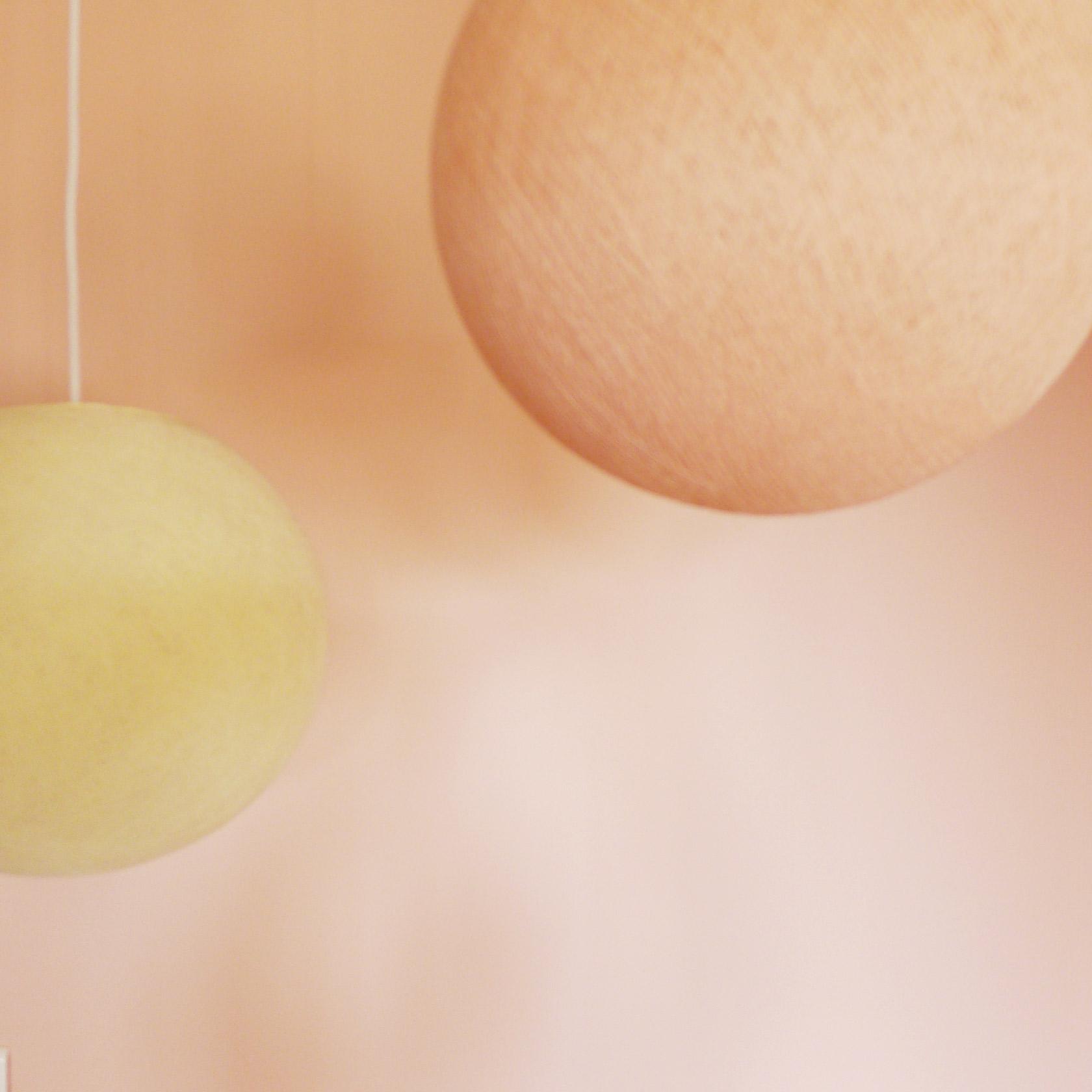 Suspensions multiples colorées dans les tons de rose et beige.