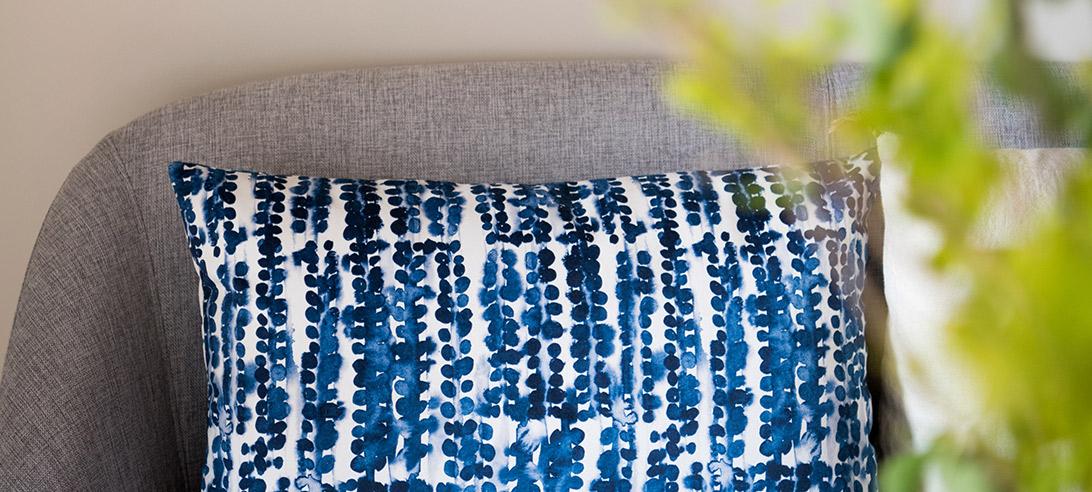 Réalisation du studio d'architecture et de décoration Skéa Designer. Projet de décoration d'intérieur. Vue d'un coussin à motif bleu Rosanna Spring création sur son fauteuil gris.