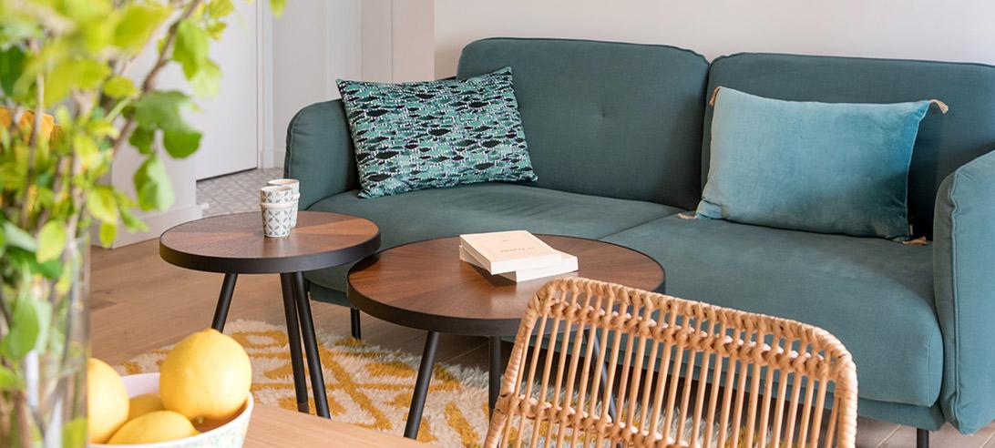 Réalisation du studio d'architecture et de décoration Skéa Designer. Un canapé bleu canard, deux tables basses. Une chaises en osier.