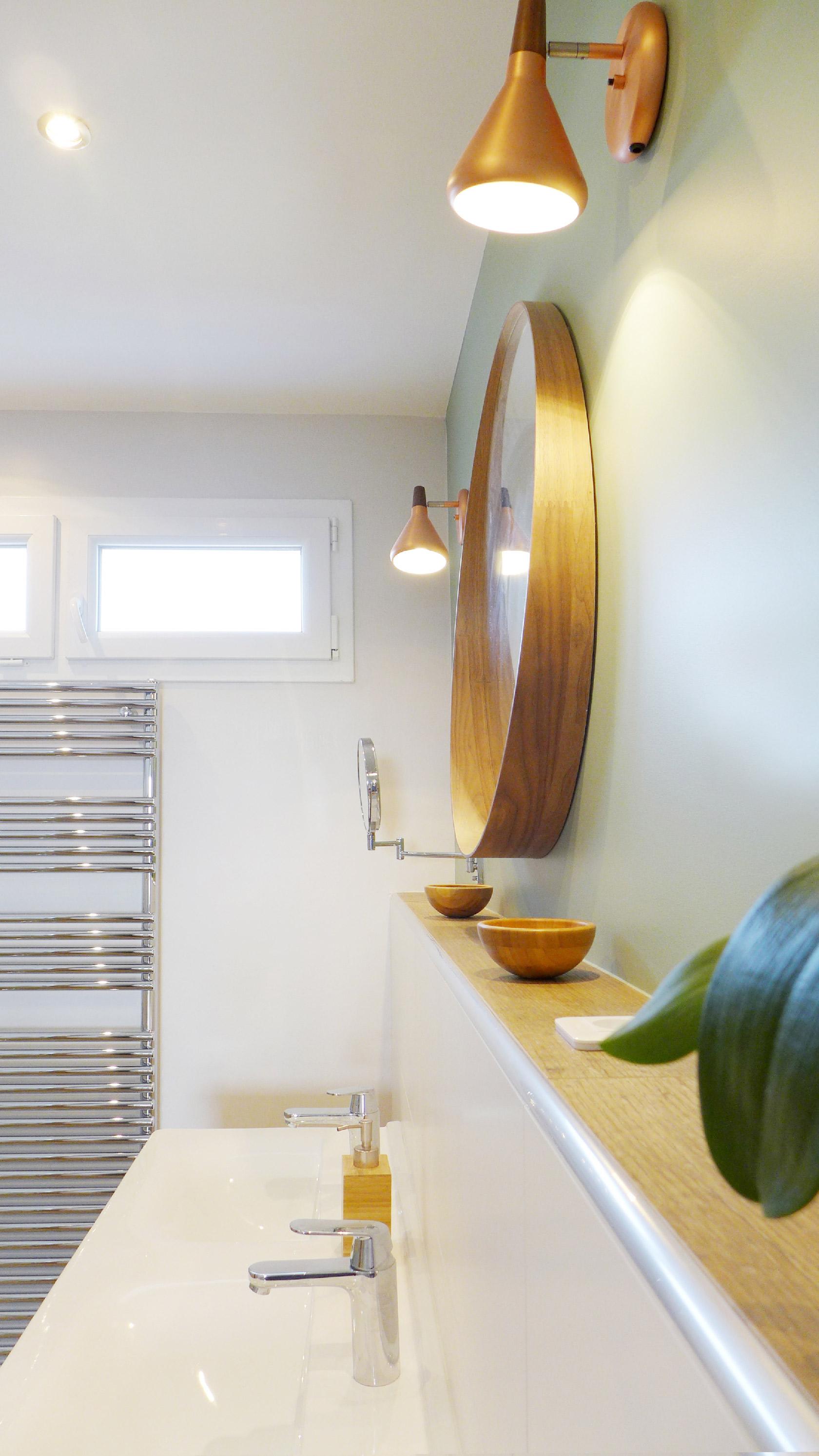 La double vasque en bois est posée sur un muret, surplombé d'un miroir. Le mur est peint en vert amande.