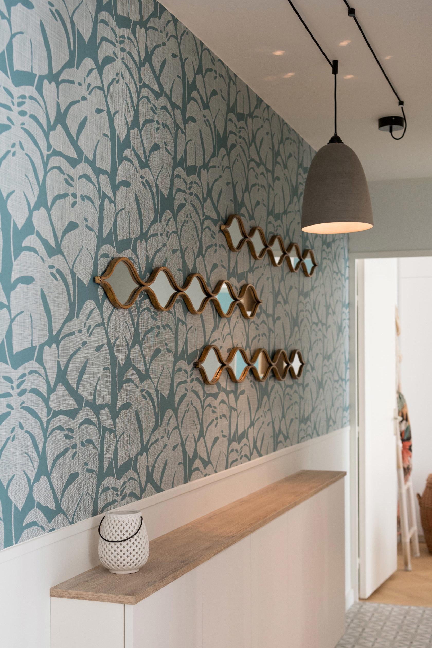 Les miroirs dorés apportent la touche finale au papier peint Missprint Guatemala et le dessin de ses feuilles de palmiers. Le meuble de rangement sur mesure permet beaucoup de rangements dans l'entrée.