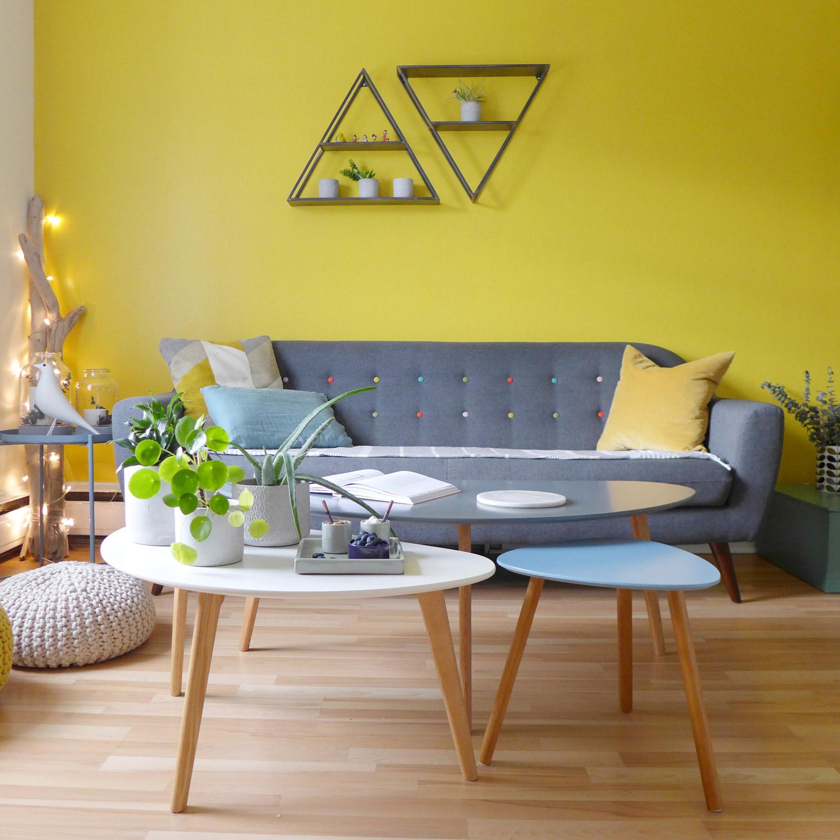 Réalisation du studio d'architecture et de décoration Skéa Designer. Jaune soleil. Le salon avec son mur jaune, son canapé gris, ses tables basses et ses poufs crochets.