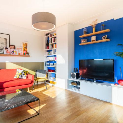 Réalisation du studio d'architecture et de décoration Skéa Designer. Inspiration Mondrian. Dans le salon, le meuble sur mesure blanc prend place devant un mur bleu électrique.