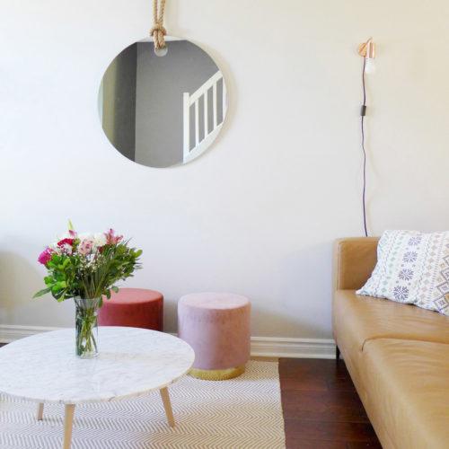 Réalisation du studio d'architecture et de décoration Skéa Designer. Velouté. Un canapé en cuir cognac, deux poufs en velours rose et orange, une table basse en marbre et un tapis composent le salon.