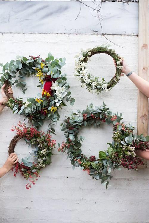 Inspiration. Couronne de fleurs. Vue de plusieurs couronnes de fleurs montées sur des branchages groupés en rond orné de branches d'eucalyptus et de fleurs fraîches ou séchées.
