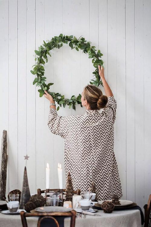 Inspiration. Couronne de laurier. Vue d'une femme en train d'accrocher une couronne de laurier sur un mur blanc.