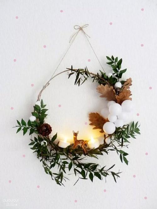 Inspiration. Couronne avec figurine. Vue d'une couronne de Noël en métal filaire arrondi avec quelques feuillages et une figurine de biche. Très bohème.