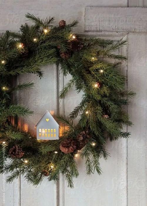 Inspiration. Couronne de Noël. Vue d'une couronne de Noël ronde en sapin avec au centre, une maison en papier découpé. Une valeur sûre.