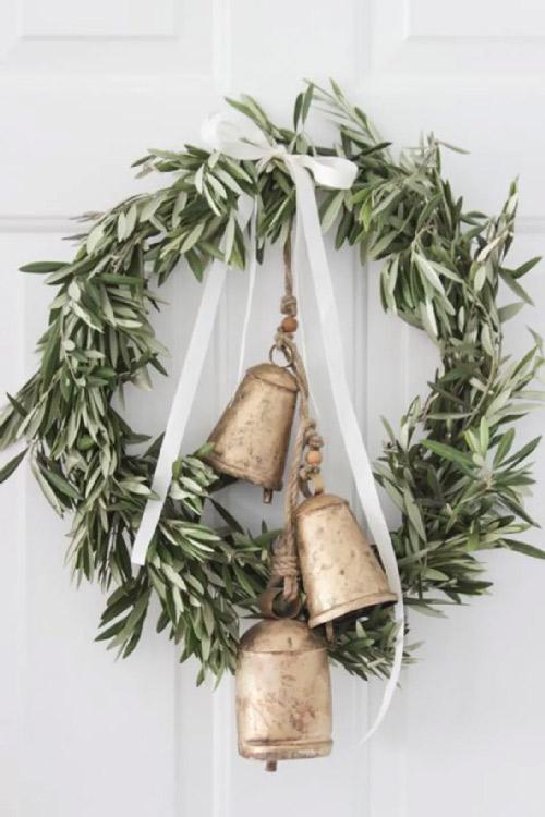 Inspiration. Couronne de Noël. Vue d'une couronne de Noël en branches d'olivier avec des cloches dorées et un ruban de satin blanc. Très chic.