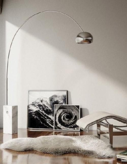 v Avec son piétement en marbre et son arc argenté, le lampadaire éclaire la pièce.