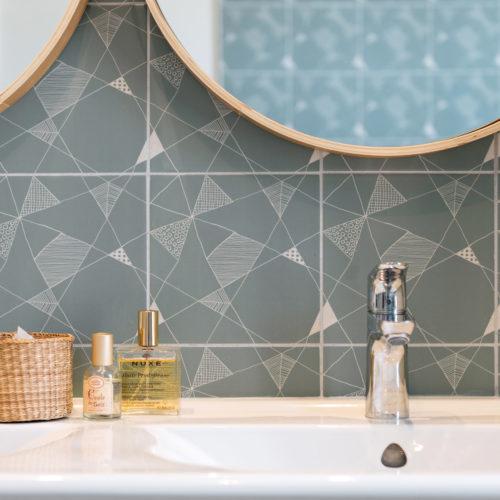 Praline bleue. Réalisation du studio d'architecture et de décoration Skéa Designer. Rénovation d'une maison des années 1930. Une salle de bain dans les tons de bleu : carrelage à motif géométrique, double vasque bois, miroirs ronds, colonnes de rangement, tablier de baignoire bois.