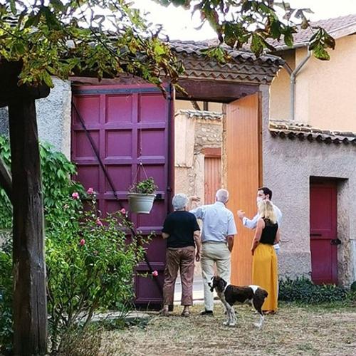Echange entre propriétaires des lieux dans la cours de la maison.
