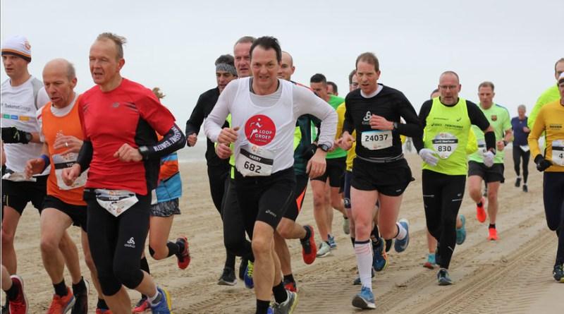 Groep op het strand tijdens de halve marathon van Egmond, Skedel verstopt in de groep