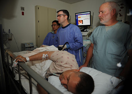 460px-US_Navy_110405-N-KA543-028_Hospitalman_Urian_D._Thompson,_left,_Lt._Cmdr._Eric_A._Lavery_and_Registered_Nurse_Steven_Cherry_review_the_monitor_whil