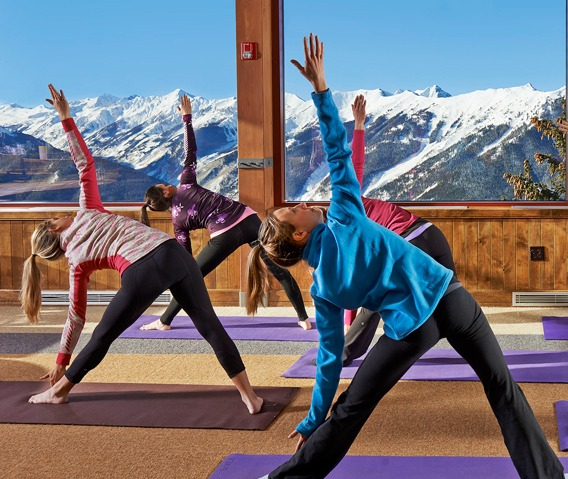 Yogis start the day right with pre-skiing and -riding stretching at the top of Aspen Mountain. | Photo: Aspen Snowmass