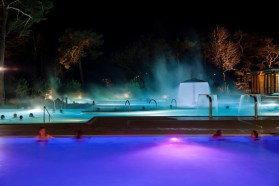Taking a dip at night is just as beautiful with the glowing water lights. | Photo: Les Bains de Lavey Spa