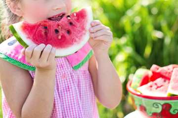 A young girl eating a slice of watermelon on a summers day.