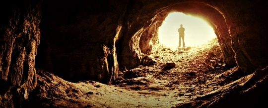 Man Standing At Cave Entrance