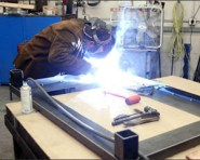 Skills employee welds a leg onto a coffee table, 2003. Photo courtesy of Seattle Post-Intelligencer.