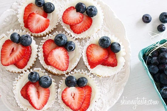 Mini cheesecake cupcakes made with Greek yogurt and cream cheese with a vanilla wafer crust topped with strawberries and blueberries to create a red, white and blue dessert using Mother Nature as my source for food coloring.