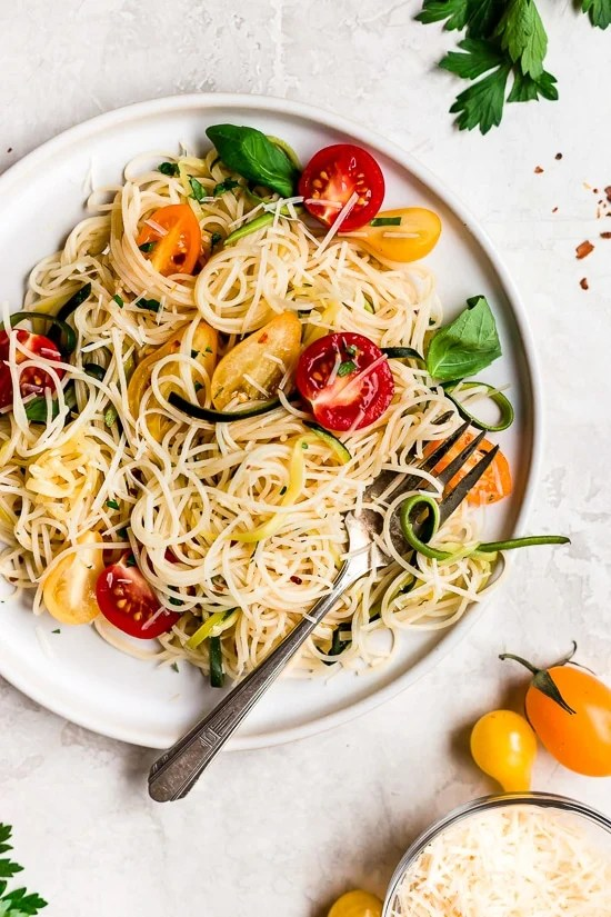 Angel hair pasta tossed with summer zucchini and tomatoes fresh from the garden. The perfect meatless meal you'll be craving again and again. Serve this with plenty of Parmigiano Reggiano!