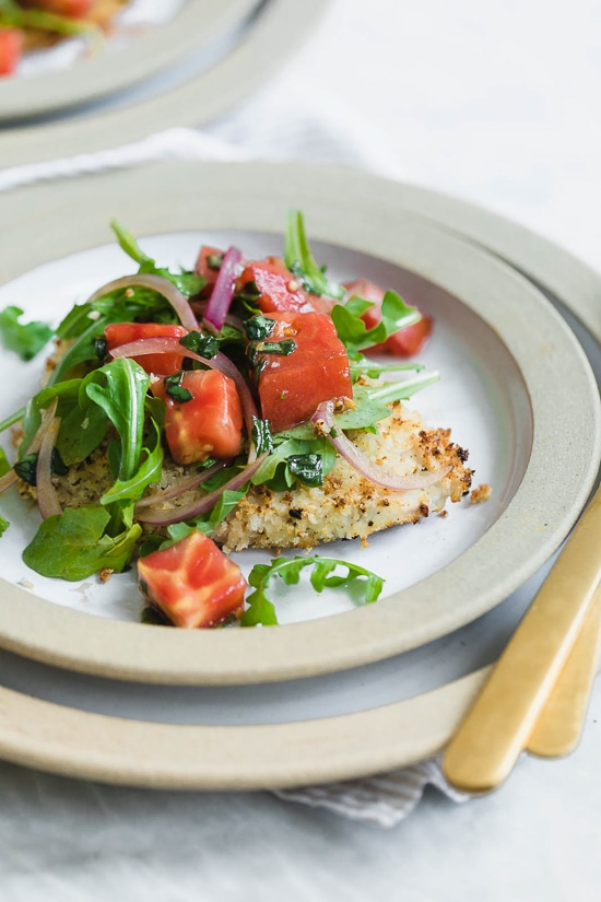 Baked Chicken Milanese is made with breaded chicken cutlets, baked in the oven topped with arugula, tomatoes and balsamic. This is my favorite restaurant dish, made healthier!