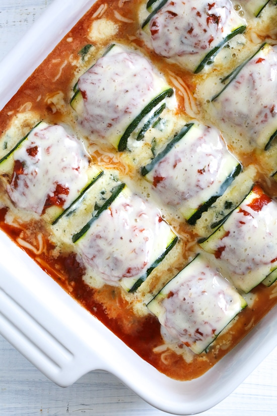Noodle-less Zucchini Rollatini is low-carb and delicious! Made with strips of grilled zucchini stuffed with a basil-cheese filling, then rolled and topped with marinara, mozzarella and baked in the oven until the cheese is hot and melted.
