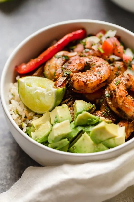 These Shrimp Fajita Bowls are a tasty and easy dinner that your whole family will love! Served over a bed of cilantro-lime rice with peppers and onions, avocado and salsa.