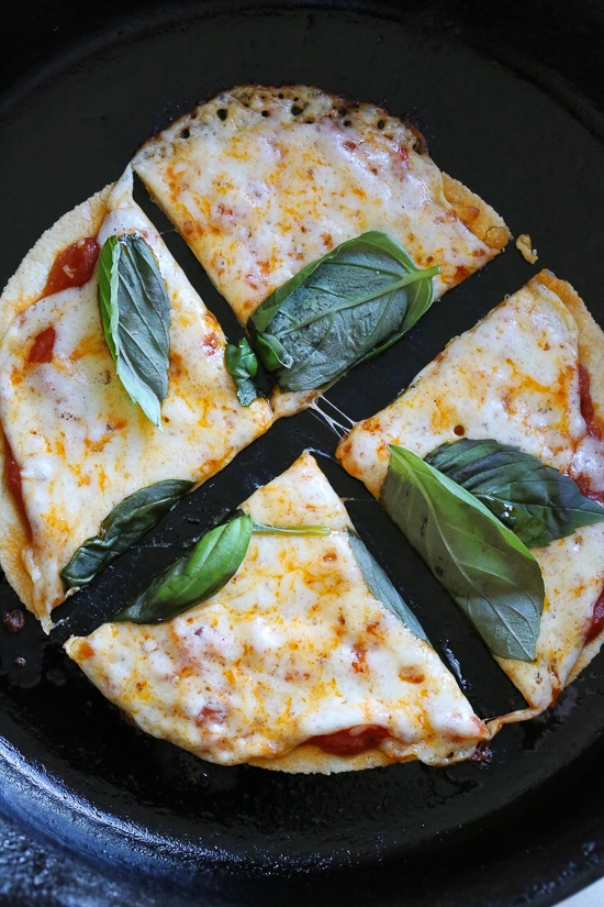 I'm obsessed with this Super-Quick Cast-Iron Pizza technique made with tortillas.This combined stove top and oven recipe comes out just like Domino's or any bar thin crust pizza!