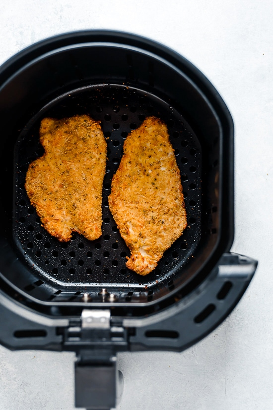 Air Fryer Chicken Cutlets with Arugula and lemon wedges is one of my favorite dinners!