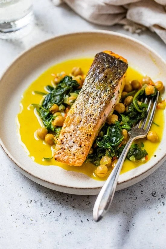 salmon on a plate with spinach and chickpeas