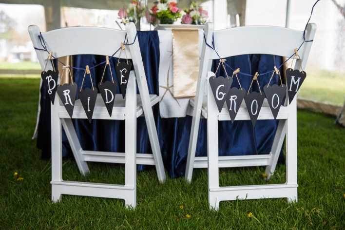 Chalkboard pennant flags were hung on the couple's chairs with navy raffia and mini clothespins. Signs by SKO Designs. Photography by Organic Photography.