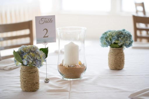 Beach Theme Centerpieces. Rope containers, Candle centerpieces & Table Cards by SKO Designs. Flowers by Katydid Flowers. Sea Crest Beach Hotel in Falmouth, Cape Cod, Mass. Photography by Nicole Lopez Photography.