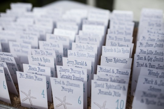 Starfish Place cards by SKO Designs stood up in a tray of beach sand. Photography by Organic Photography.
