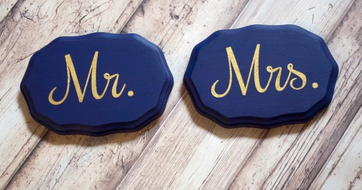 Wavy oval wooden chair signs painted navy blue with metallic gold painted letters saying Mr. & Mrs.